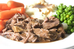 Pot roast dinner  potatoes carrots green peas Royalty Free Stock Photos