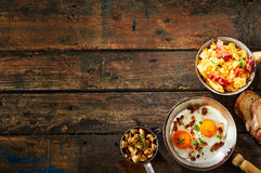 Pot of scrambled eggs and bacon on rustic table Stock Photos