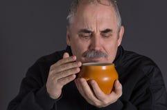 Pot sentant de poterie de terre d'homme caucasien avec la nourriture sur le fond foncé Images libres de droits