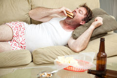 Pot Smoker with the Munchies. Unemployed middle aged man at home on the couch in his underwear, eating a hamburger, with a marijuana joing in the ashtray and royalty free stock photos