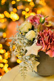 Pot of snowy pink roses and hydrangea as christmas decoration tree on bokeh lights Royalty Free Stock Images