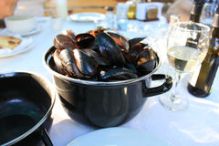 A Pot with Steamed Mussels. A black iron pot with steamed mussels in shells with a glass of white wine aside Royalty Free Stock Photography