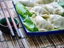 Pot Stickers or Chinese Dumplings. Asian pot stickers or Chinese dumplings on a bed of lettuce with dipping sauce and chopsticks on a bamboo mat stock photos