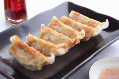 Pot Stickers with Dumpling Sauce and Chili Oil. Baked dumpling Gyoza with minced pork and vegetable stuffing. Gyoza are usually eaten with dipping sauce made at royalty free stock photo