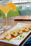 Pot stickers with an orange martini. On a bright table stock images