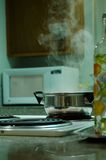 Pot in the stove. Pot with boiling water standing in the stove Stock Image