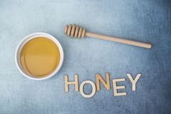 Pot of sweet honey with honey drizzle and the word honey. On a blue background Royalty Free Stock Images