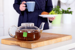Pot of tea and woman holding a healthy breakfast Royalty Free Stock Photos