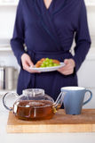 Pot of tea and woman holding a healthy breakfast Stock Image