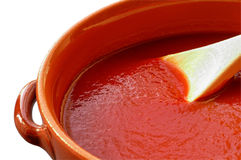 Pot with tomato sauce. Terracotta pot and wooden spoon with tomato sauce. With clipping path Royalty Free Stock Image
