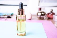 Pot transparent d'or jaune en verre avec de l'huile d'amorce, base de maquillage sur le fond d'une table de maquillage pour la be photos stock