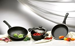 Veggie into pot and pans. A pot and two pans on a white table and background. some broccoli, tomatoes and peppers are inside and some put aside royalty free stock images