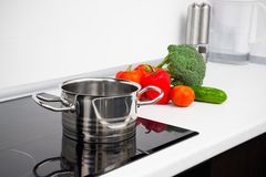 Pot and vegetables in modern kitchen Stock Images