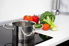 Pot and vegetables in modern kitchen Royalty Free Stock Photography
