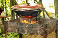 Pot water on the fire. Tourist boiler with food standing on the grill over the fire. Focus on the pot Stock Photography