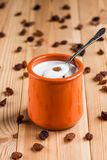 Pot of yogurt with raisins. On a wooden table board stock photos