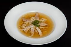 Potage au poulet dans un plat blanc sur un fond noir photo libre de droits