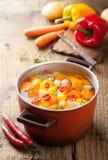 Potage aux légumes dans le pot rouge image stock