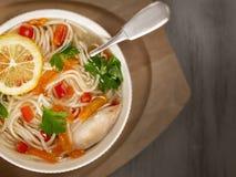 Potage aux légumes fait maison de poulet avec le citron, la carotte et les pâtes image stock