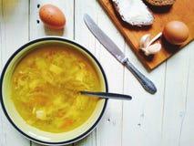 potage aux légumes, pain et beurre, oeufs, une tasse de thé et ail sur la table Images libres de droits