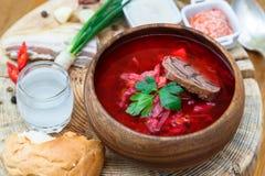 Potage aux légumes russe ukrainien traditionnel, borsch avec des butées toriques d'ail, pampushki sur un fond en bois blanc Images libres de droits