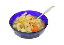 Potage et cuillère de poulet dans la cuvette bleue Photos stock
