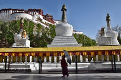 LHASA, TIBET AUTONOMOUS REGION, CHINA - CIRCA MAY 2018: A monk with the parasol walking along tibetan prayer wheels, Potala Palace royalty free stock images
