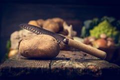 Potatis med kniven på den lantliga trätabellen, kökplats arkivbilder