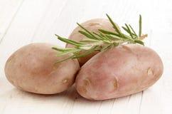 Potatis och rosmarin på den vita tabellen Arkivfoton