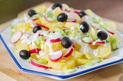 Potatis och yoghurtsallad med svarta oliv och rädisan Arkivbild