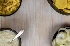 Potatis, ost, bechamelsås och lök på en vit gammal suddig bakgrund royaltyfria foton