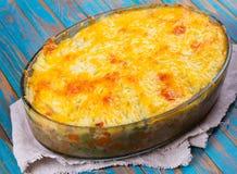 Potatis, ost, kött, morot, lök och eldfast form för gröna ärtor arkivbild