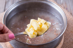 Potatisar i en sked i soppa Arkivbilder