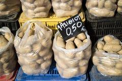 Potatisar i plastpåsar på ett grekiskt stånd Royaltyfri Bild