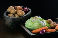 Potatisar, lökar, morötter och kål i träbunkar Arkivfoto