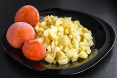 Potatisar och tomater på en svart platta Royaltyfri Fotografi