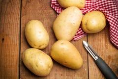Potatisar på en trätabell Royaltyfria Bilder