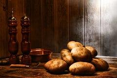 Potatisar på gammalt trä bordlägger i ett antikt kök Royaltyfria Bilder
