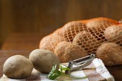 Potatisar som är ut ur jutepåsen som är klar att skalas Arkivbilder