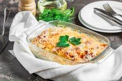Potatisar som lagas mat i ugnen som bakas med äpplen, ost och nytt Royaltyfri Bild