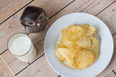 Potatischiper med mjölkar på träbakgrunder Arkivfoton