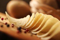 Potatischiper på en träkubb arkivfoton