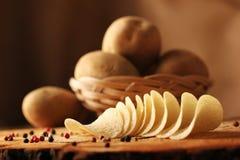 Potatischiper på en träkubb royaltyfri fotografi