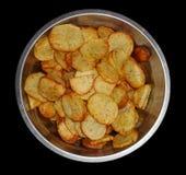 Potatischiper på svart bakgrund Royaltyfri Foto