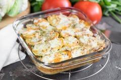 Potatiseldfast form med gräddfilsås, tomater, persilja, cauli Royaltyfri Bild