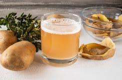 Potatisfruktsaft i ett exponeringsglas nära den hela potatisen och skarlupaen arkivbilder
