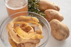 Potatisfruktsaft i ett exponeringsglas nära den hela potatisen och skarlupaen royaltyfri bild