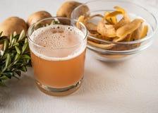 Potatisfruktsaft i ett exponeringsglas nära den hela potatisen och skarlupaen royaltyfri foto