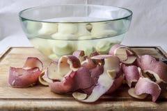 Potatispeels och potatisar i vatten från sida royaltyfri bild