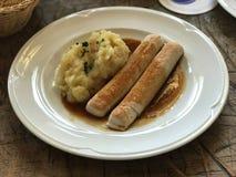 Potatissallad och korvar i bayersk kokkonst för sky Arkivfoto